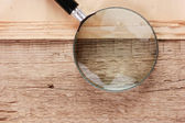 Edge of the old newspaper and magnifying glass on a wooden backg — Stock Photo