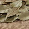 Dry bay leaf on old wooden board — Stock Photo #23998753