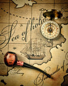 Old tobacco pipe and a compass on the map — Stock Photo