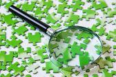 Förstoringsglas på grön pussel — Stockfoto