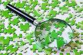 Magnifying glass on the green puzzle — Zdjęcie stockowe