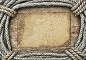 Frame made of twisted rope and old paper on a wooden background — Stock Photo