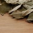 Dry bay leaf on wooden kitchen cutting board — Stock Photo #24279847