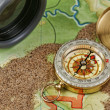 Binoculars and a compass on the map with sand — Stock Photo #24279869