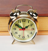 Golden alarm clock on the book — Stock Photo