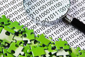 Puzzles and magnifying glass on a binary code — Stock Photo
