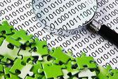 Quebra-cabeças e lupa em um código binário — Foto Stock