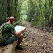 Travelling man sitting and looking at the map in the bamboo fore - Stockfoto