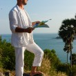 A young man in a white suit standing on sea shore with a map - Stockfoto