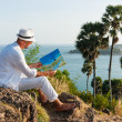 A young man in a white suit sitting on the beach with a map - Stockfoto