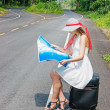 A young girl sitting on a suitcase with a map in hand — Stock Photo #24333653