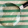 Collage cut from newspaper  and magnifying glass on green backgr — Stock Photo