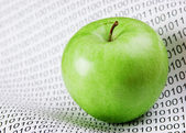 Green apple on a binary code — Stock Photo