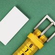 Meter belt slimming and blank business card on the green backgro — Stock Photo #24453783