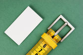 Meter belt slimming and blank business card on the green backgro — Stock Photo