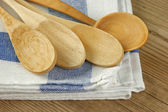 Wooden kitchenware and dishcloth on old wooden table — Stock Photo