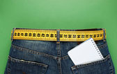 Jeans with meter belt slimming and notebook in pocket on the gre — Stock Photo