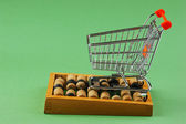 Shopping cart and abacus on the green background — Stock Photo