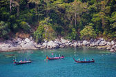 Traditional longtail boats and tourists snorkel in Thailand — Stock Photo