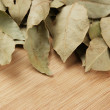 Dry bay leaf on wooden kitchen cutting board — Stock Photo #25062991