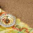 Stock Photo: Compass on map with sand
