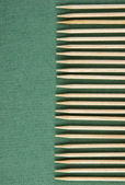 Wooden toothpicks on the green background — Stock Photo