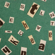 Stock Photo: Collage word cut from newspaper on green background