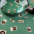 Letters cut from newspaper and magnifying glass on green backgro - Stock Photo
