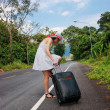 Young girl walking down the road with a suitcase — Stock Photo
