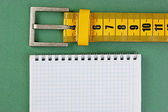 Meter belt slimming and notepad on the green background — Stock Photo
