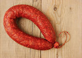 Krakow sausage isolated on the wooden table — Stock Photo