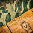 Old hunting cartridges and bandoleer on camouflage background — Stock Photo