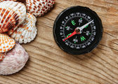 Sea shells and compass on old wooden board — Stock Photo