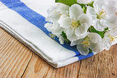 Table-napkin and bird cherry branch on a wooden background — Stock Photo