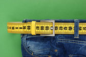 Jeans mit meter-gürtel abnehmen auf grünem hintergrund — Stockfoto