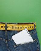 Jeans mit gürtel abnehmen und notebook in der tasche auf den gre — Stockfoto