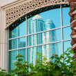 Reflection of modern high-rise buildings in window - Stock Photo