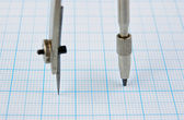 Drawing compass on graph paper — Stock Photo