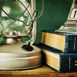Photo: Old kerosene lamp and a stack of books