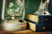 Old kerosene lamp and a stack of books — Stock Photo