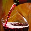 Red wine being poured into wine glass — Stock Photo #25926575