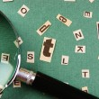 Stock Photo: Letters cut from newspaper and magnifying glass on green backgro