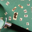 Letters cut from newspaper and magnifying glass on green backgro — Stock Photo