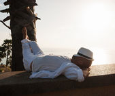 A young man in a white suit lies on the waterfront — Stock Photo