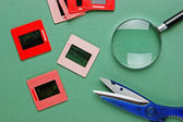 Old slides and a magnifying glass on green table — Stock Photo