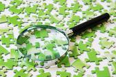 Lupe auf das grüne puzzle — Stockfoto