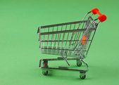Shopping cart on the green background — Stock Photo
