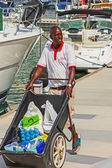 Black man with a cart full of supplies — Stock Photo