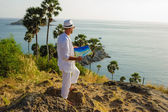 A young man in a white suit on the beach with a map — Stock Photo