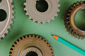 Gears and pencil on a green background — ストック写真